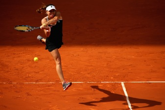 MADRID, SPAIN - MAY 02: Alexandra Dulgheru of Romania leaps to play a backhand against Ana Ivanovic of Serbia in their first round match during day one of the Mutua Madrid Open tennis tournament at the Caja Magica on May 2, 2015 in Madrid, Spain. (Photo by Clive Brunskill/Getty Images)